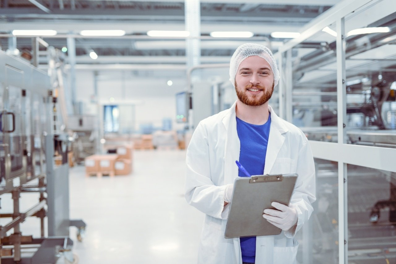 Scientist With Clipboard Posing in Factory_iStock-866799478-252813-edited