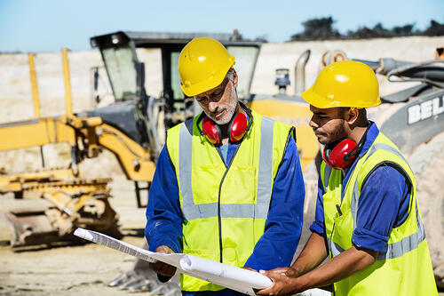 Construction-workers-examining-blueprint-at-quarry